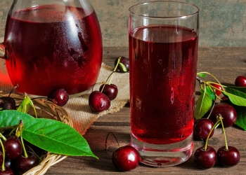 cold cherry juice in a glass and pitcher on wooden table with ripe berries in wicker basket; Shutterstock ID 447393178; Purchase Order: -